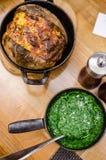 菠菜和parmiggiana纯汁浓汤,被烘烤的土豆 免版税图库摄影