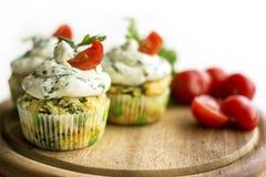 菠菜杯形蛋糕用乳酪提取乳脂结霜和绿色新鲜的葱在木板 免版税库存图片