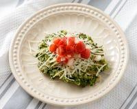 菠菜油炸馅饼冠上用蕃茄和乳酪 库存图片