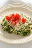 菠菜油炸馅饼冠上用蕃茄和乳酪 免版税库存图片