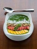 菠菜鲕梨smothie碗用果子和坚果在上面 库存图片