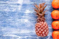 菠萝和桔子在蓝色书桌背景顶视图空间文本的 库存图片