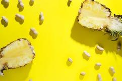 菠萝和花生顶视图与长的阴影在明亮的黄色背景,空的空间文本的 免版税库存照片