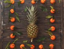 菠萝和蜜桔土气木背景 顶视图 免版税库存图片
