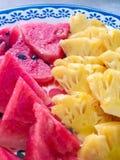 菠萝和西瓜在白色盘在夏天 免版税库存图片