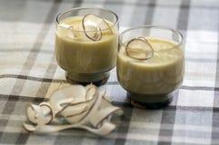 菠萝圆滑的人用香蕉, oatmeals和椰奶,装饰用椰子切削,方格的桌布 免版税库存照片