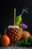 菠萝杯子在黑背景的multifruit汁液 椰子、薄菏和柑橘水果在饮料附近 免版税图库摄影
