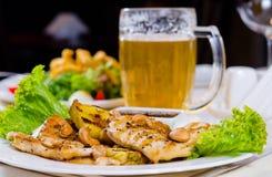 菠萝腰果与杯子的鸡肉菜肴啤酒 免版税库存图片