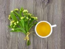 菩提树花和茶杯逗人喜爱的花束在木桌上 平的位置,顶视图 免版税库存图片
