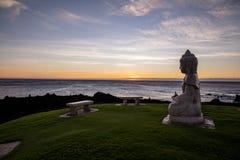 菩萨一个平静的雕象坐太平洋观看的日落岸  库存图片
