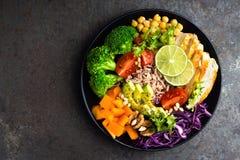 菩萨与鸡内圆角,糙米,鲕梨,胡椒,蕃茄,硬花甘蓝,红叶卷心菜,鸡豆,新鲜的莴苣沙拉, p的碗膳食 库存照片