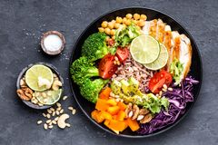 菩萨与鸡内圆角,糙米,鲕梨,胡椒,蕃茄,硬花甘蓝,红叶卷心菜,鸡豆,新鲜的莴苣沙拉, p的碗盘 免版税库存照片