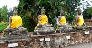 菩萨在阿尤特拉利夫雷斯泰国向以黄色穿戴的雕象扔石头 免版税库存照片