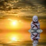 菩萨在水中反射了在日出 免版税库存照片