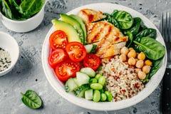 菩萨碗用菠菜沙拉,奎奴亚藜,鸡豆,烤了鸡,鲕梨,蕃茄,黄瓜,芝麻籽 免版税库存照片