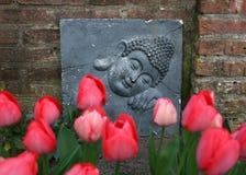 菩萨装饰和红色郁金香在庭院里 免版税库存照片