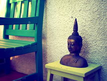 菩萨装饰品和绿色椅子 免版税库存照片
