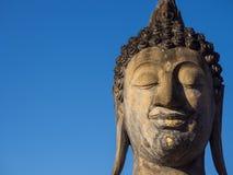菩萨雕象与天空蔚蓝背景艺术宗教的面孔画象 免版税库存图片
