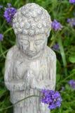 菩萨雕象在淡紫色庭院里 免版税库存照片