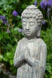 菩萨雕象在淡紫色庭院里 免版税图库摄影