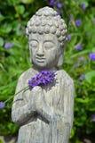 菩萨雕象在淡紫色庭院里 免版税库存图片