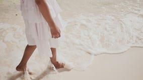 菲律宾女小学生的赤裸和被晒黑的腿一件白色礼服的在白色沙子走,接触泡沫似的波浪  股票视频
