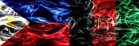 菲律宾对阿富汗,肩并肩被安置的阿富汗尼的烟旗子 重摘要色的柔滑的烟旗子 库存图片