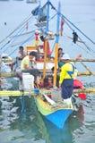 菲律宾渔夫在一个渔船工作 免版税库存图片