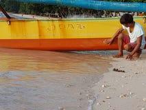 菲律宾渔夫清洗并且准备他的小船 免版税库存图片