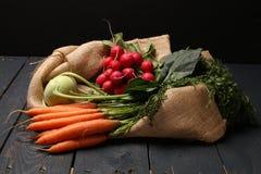 萝卜、撇蓝和红萝卜在木背景和黄麻请求 免版税库存照片