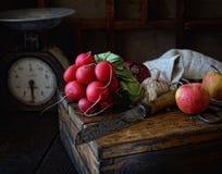 萝卜束,刀子,在一个木箱的苹果,在黑暗的背景的葡萄酒标度 库存图片
