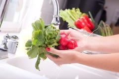 萝卜洗涤的妇女 免版税库存图片