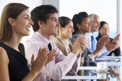 营业范围听介绍的人供以座位在玻璃会议室表上 免版税库存照片