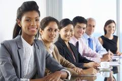 营业范围听介绍的人供以座位在玻璃会议室表上 免版税库存图片