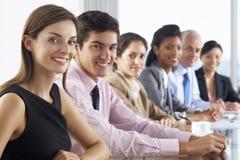 营业范围听介绍的人供以座位在玻璃会议室表上 图库摄影