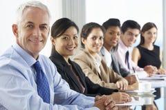 营业范围听介绍的人供以座位在玻璃会议室表上 库存图片