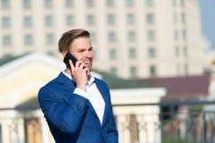 营业通讯和新技术 与智能手机的愉快的商人在晴朗的大阳台 在正式衣服的人微笑与MOBIL 库存照片