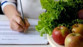 营养师妇女文字在充分桌上的饮食计划水果和蔬菜 股票录像