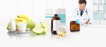 营养师营养师医生规定坐在书桌办公室的处方用苹果、酸奶、医疗药物和磁带米 免版税库存照片