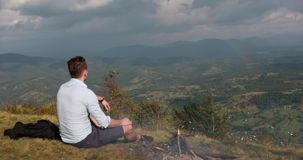 营火在坐小山的上面和观看彩虹的一个孤独的人后烧 影视素材
