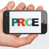 营销概念:拿着有价格的手智能手机在显示 库存图片
