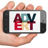 营销概念:拿着有广告的手智能手机在显示 免版税图库摄影