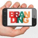 营销概念:拿着有烙记的手智能手机在显示 库存图片
