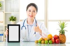 医治营养师用拿着空白的数字式片剂的果子和 免版税图库摄影