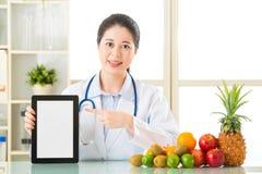医治营养师用果子和拿着数字式片剂 免版税库存图片