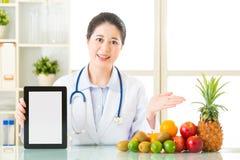 医治营养师用果子和拿着空白的数字式片剂 图库摄影