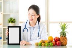 医治营养师用果子和拿着空白的数字式片剂 库存照片