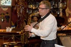 萨克斯管吹奏者,音乐家流行音乐小组鸡尾酒,亚历山大Mazurov 免版税库存图片