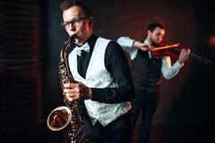 萨克斯管演奏古典曲调的人和提琴手二重奏 免版税库存图片