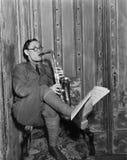 萨克管演奏员徒步读书音乐(所有人被描述不更长生存,并且庄园不存在 供应商保单那 免版税库存照片